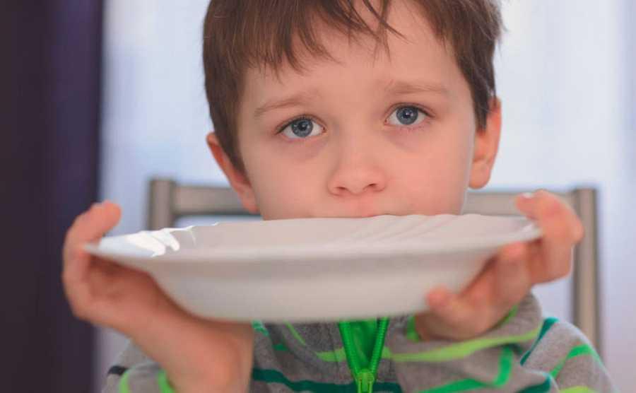 Un niño con ojos de súplica presenta un plato vacío pidiendo alimento.