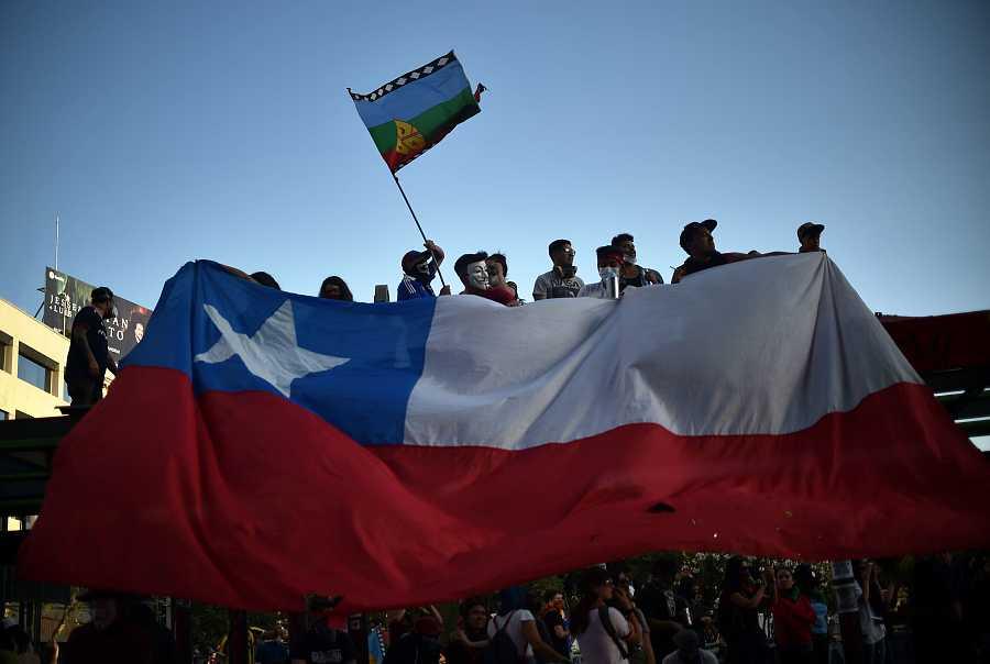 Un grupo de manifestantes enarbola una bandera chilena y otra mapuche en las protestas de Santiago