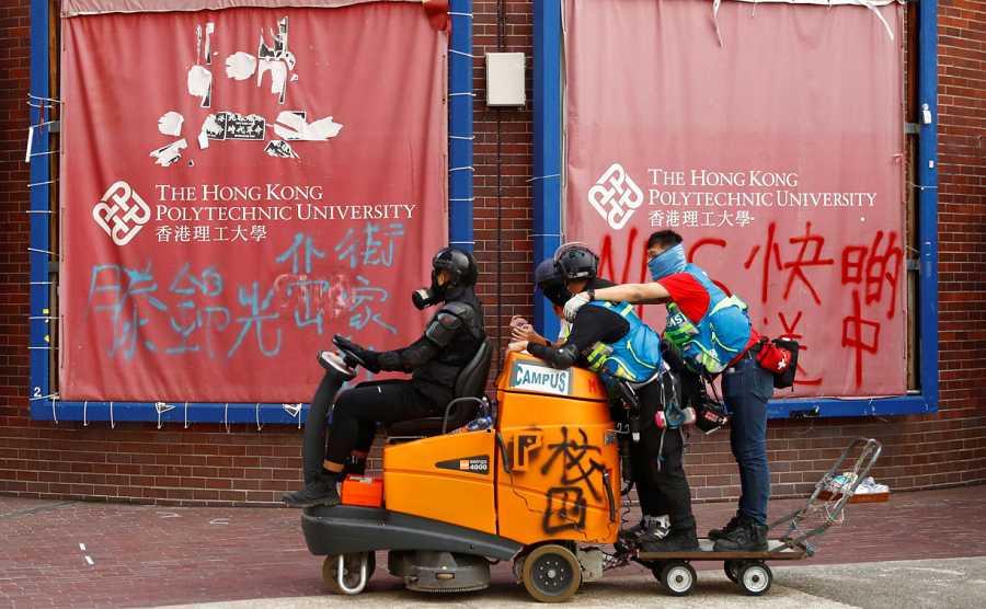 Tres manifestantes manejan un vehículo de la limpieza adaptado a la lucha callejera en el campus universitario.