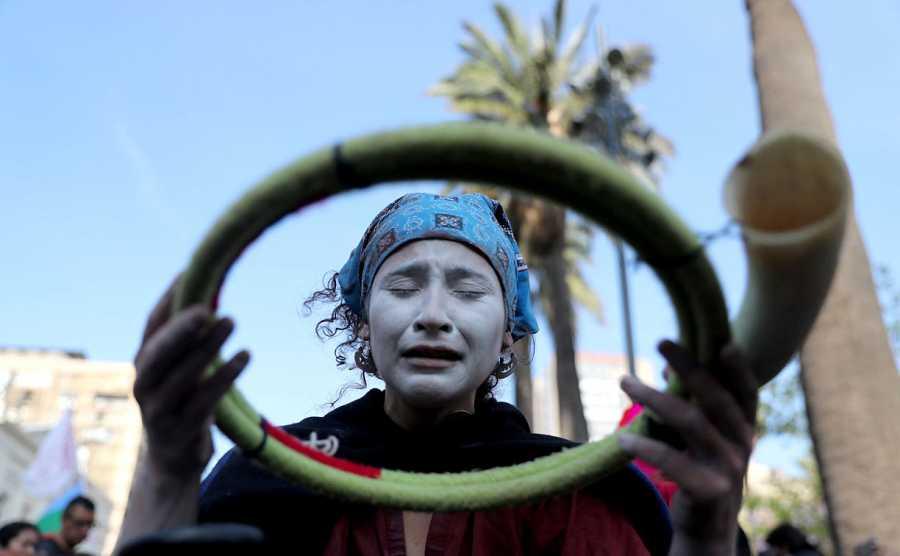 Una indígena mapuche, con la cara pintada, se prepara con uno de sus ritos antes de participar en una de las manifestaciones ciudadanas en Santiago.