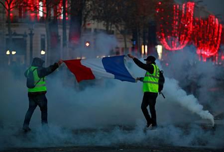 Dos manifestantes portan la bandera de Francia en los Campos Elíseos
