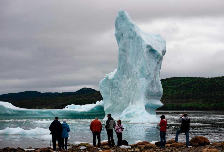 Un grupo de turistas observan un iceberg en la costa de Canadá.