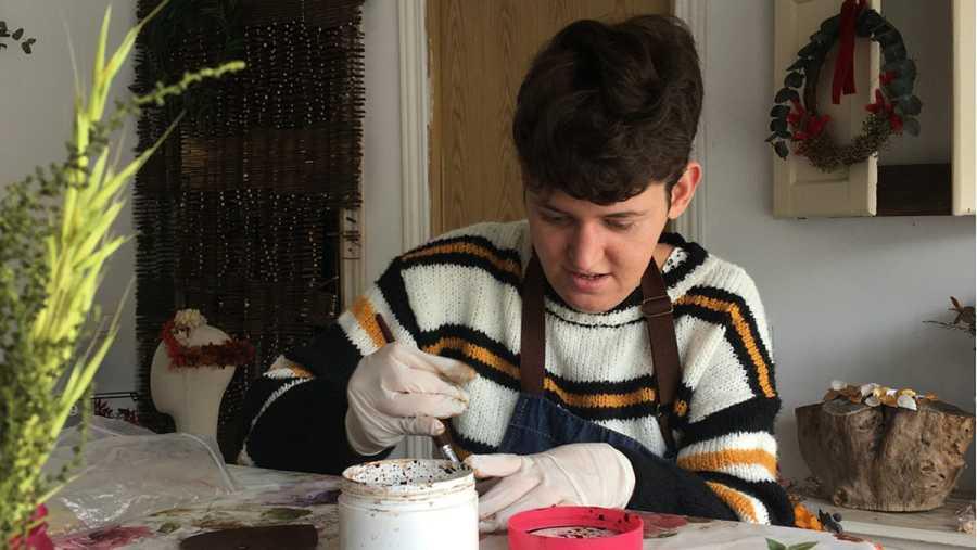 Xhulia pintando corazones de madera