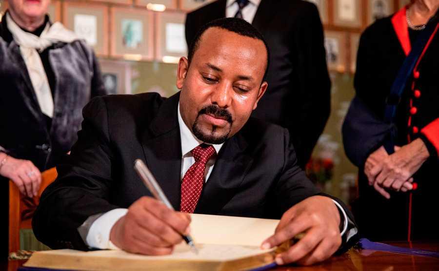 El primer ministro etíope, Abiy Ahmed, firma el libro de los galardonados a su llegada al Ayuntamiento de Oslo.