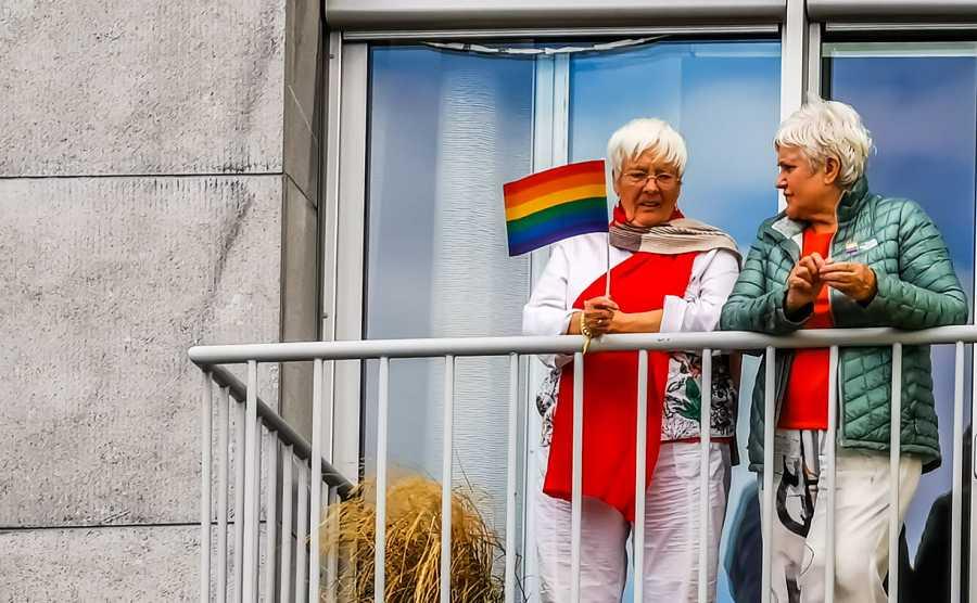 Dos mujeres mayores celebran el día del orgullo gay en un balcón con la bandera del arco iris.