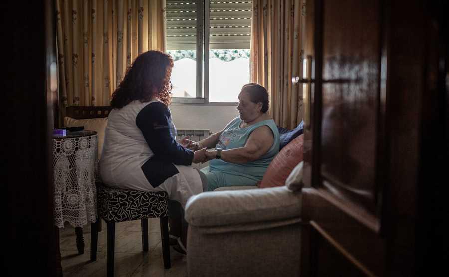 Una mujer atiende a una persona mayor en su casa.