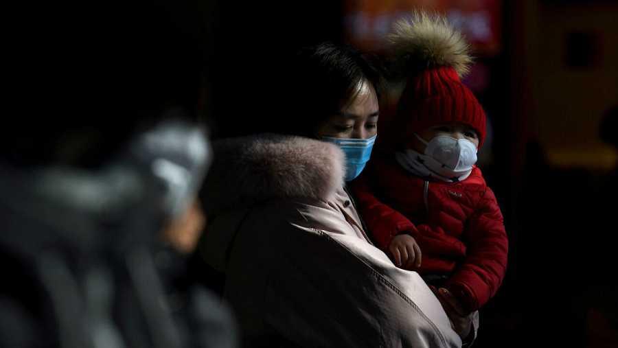 Una mujer junto a su hijo llevan máscaras para prevenir el contagio del coronavirus.