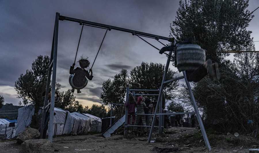 Niños juegan en un columpio a las afueras de Moria