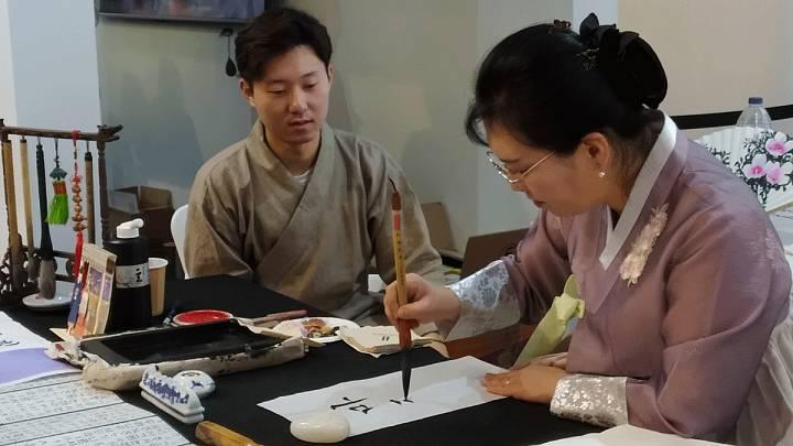 Una mujer y un hombre escriben los nombres de los asistentes  a Fitur en hagul, el alfabeto coreano.