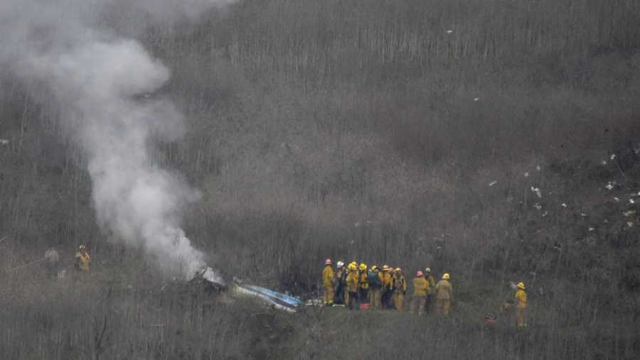 Efectivos del cuerpo de bomberos junto al helicóptero accidentado