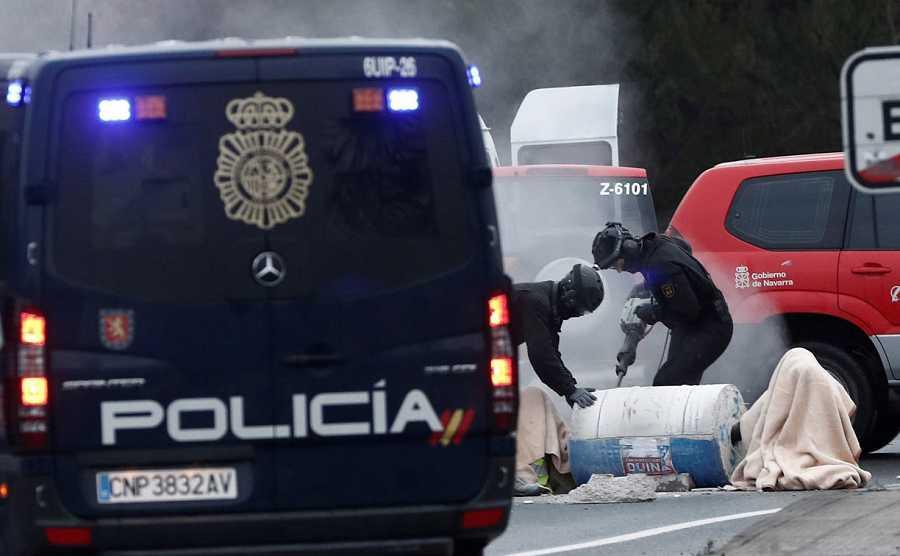 Efectivos de la Policía Nacional tratan de liberar a un grupo de personas que se han encadenado con bidones de hormigón en Pamplona, durante la jornada de huelga.