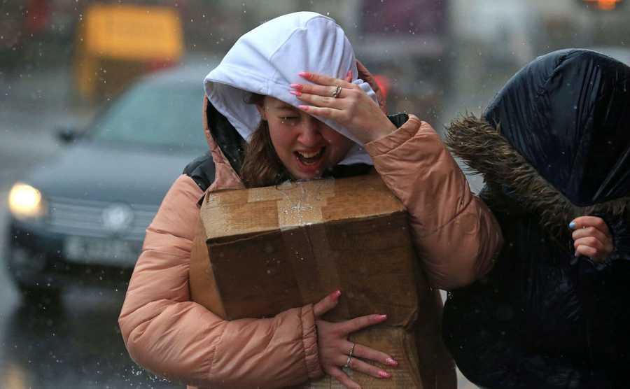 Una mujer intenta protegerse de los fuertes vientos y la lluvia en Sheffield, en el norte de Inglaterra, mientras la tormenta Ciara azota el país.
