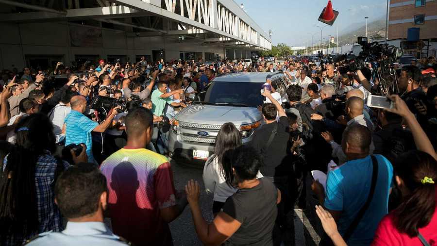 La multitud venezolana, con opositores y simpatizantes del chavismo, se han amontonado alrededor del vehículo en el que Guaidó ha abandonado el aeropuerto.