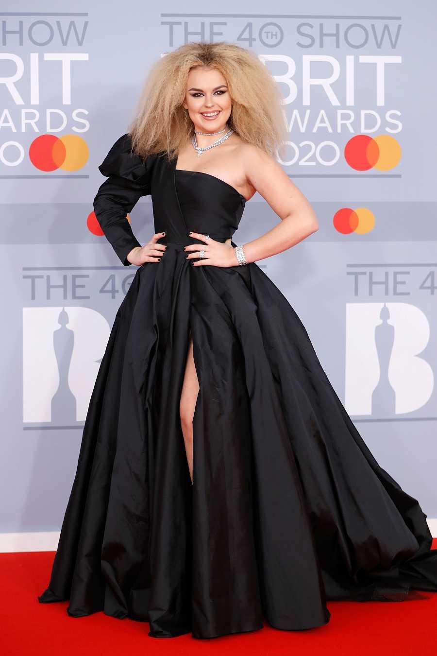 La cantante y compositora Tallia Storm en los Brit Awards con un vestido negro asimétrico con manga abullonada y falda con volumen y gran abertura central