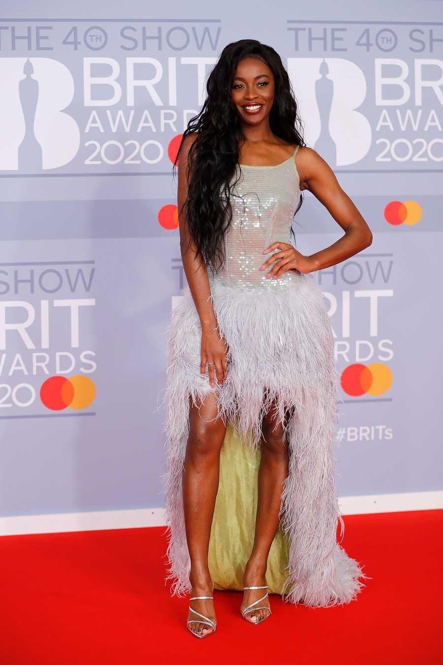 La presentadora AJ Odudu se atrevió con un vestido de tirantes asimétrico con cola. La parte superior, brillante y la falda con plumas y forro de raso en color verde pistacho