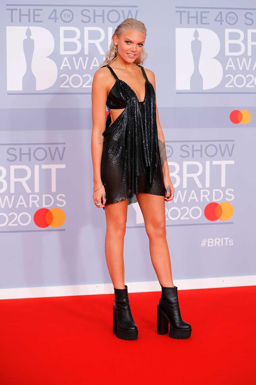 La presentadora y DJ Becca Dudley en los Brit 2020 con un vestido negro mini de tirantes y escote pronunciado combinado con unas botas planas