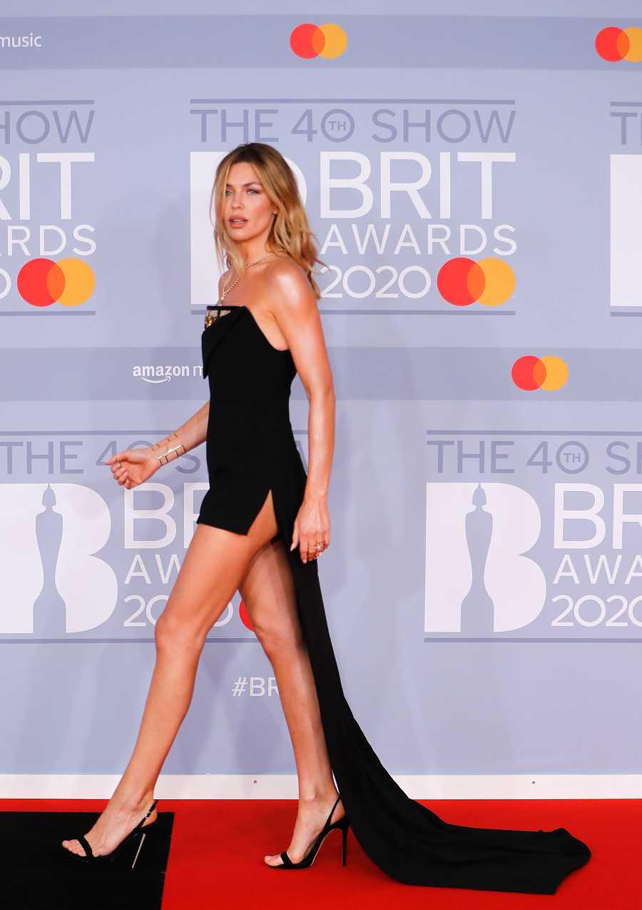 La modelo Abbey Clancy en los Brit 2020 con un vestido mini negro con larga cola