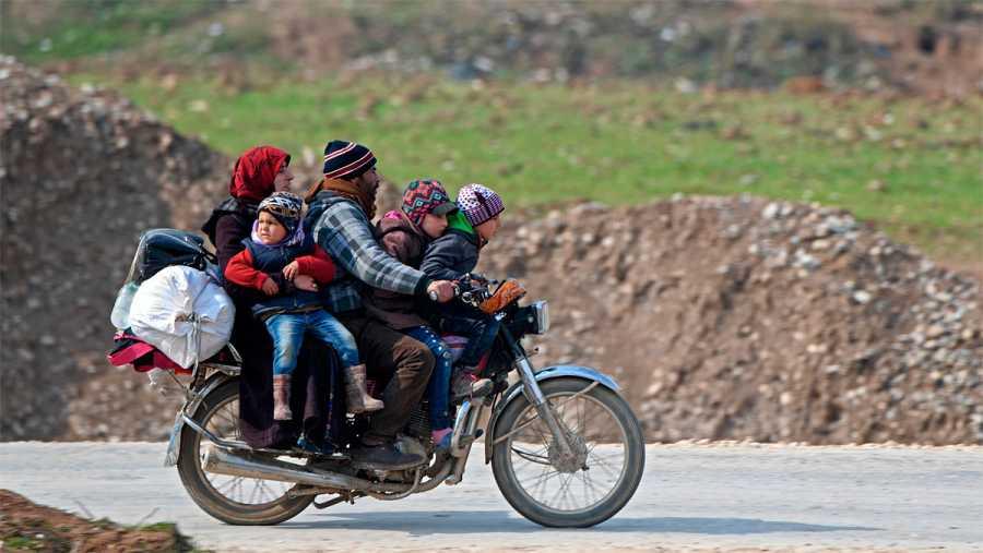 Una familia llega en motocicleta al campo de refugiados de Deir al-Ballut, cerca de la frontera siria con Turquía