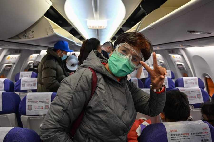 Un pasajero con mascarilla para prevenir el contagio por coronavirus, en un avión en Shanghai.