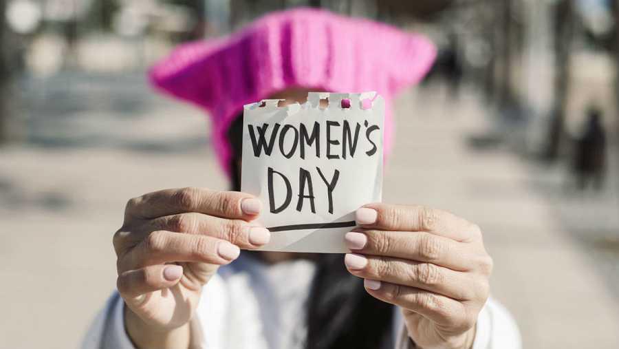 Plano detalle de una mujer sosteniendo un papel en el que se puede leer