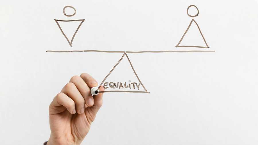 En la imagen, una persona dibuja una balanza que ejemplifica la búsqueda de la igualdad entre hombres y mujeres.