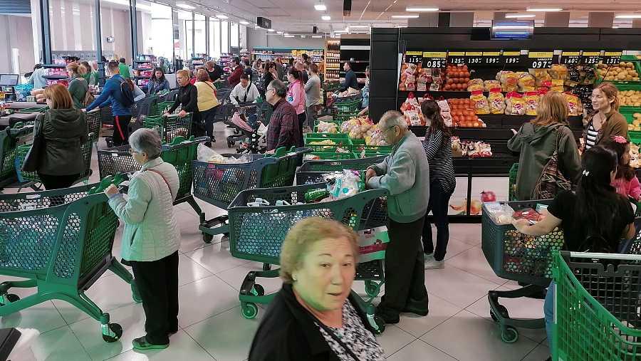 Decenas de personas hacen cola ante las cajas de un supermercado