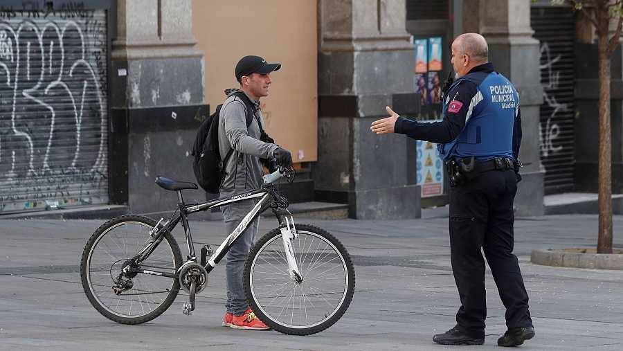 Un policía de Madrid informa a un ciudadano de la prohibición de montar en bici.