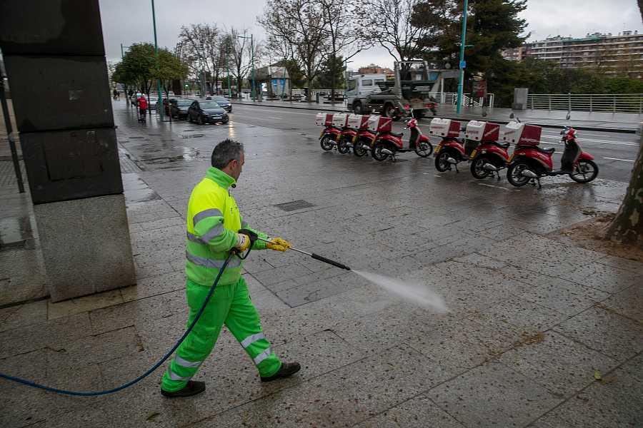 Empleados municipales limpian las calles vacías.