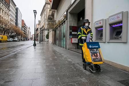 Una trabajadora del servicio de Correos realiza su trabajo por las calles casi desiertas de Zaragoza.