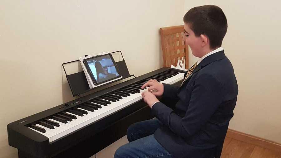 Chechu, de 12 años, sigue su clase de piano en streaming. Mantener su rutina es esencial para las personas con TEA.