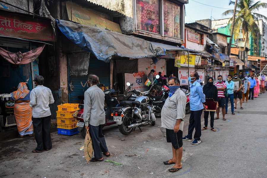 Los vecinos de Dharavi, el 'slum' más famoso de Bombay, hacen cola para comprar lecha durante el confinamiento