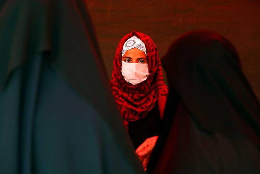 Una vendedora de productos sanitarios lleva una mascarilla para protegerse por el coronavirus
