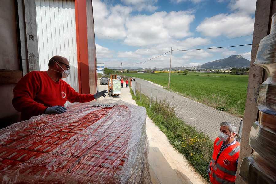 Voluntarios de la Cruz Roja descargan alimentos en el aeródromo de Igualada-Ódena (Barcelona), donde se instalará un espacio logístico humanitario para distribuir productos de primera necesidad entre las familias en riesgo afectadas por el confinamie
