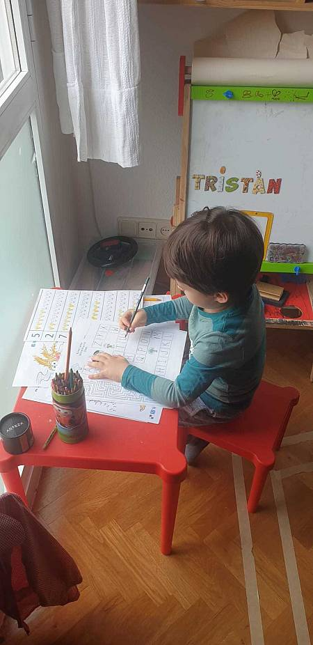 Un niño juega junto a la ventana en su quinta semana de confinamiento