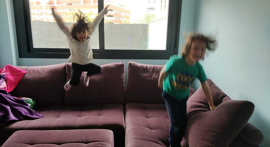 Dos niños saltan en el sofá de su casa. Relajar las normas y multiplicar la paciencia es vital para sobrellevar el confinamiento.
