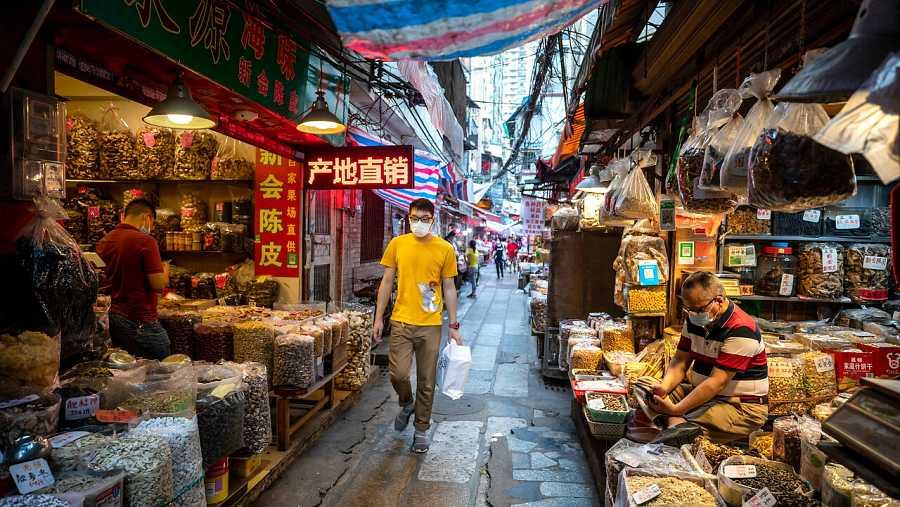 Un hombre camina por un mercado de Guangzhou