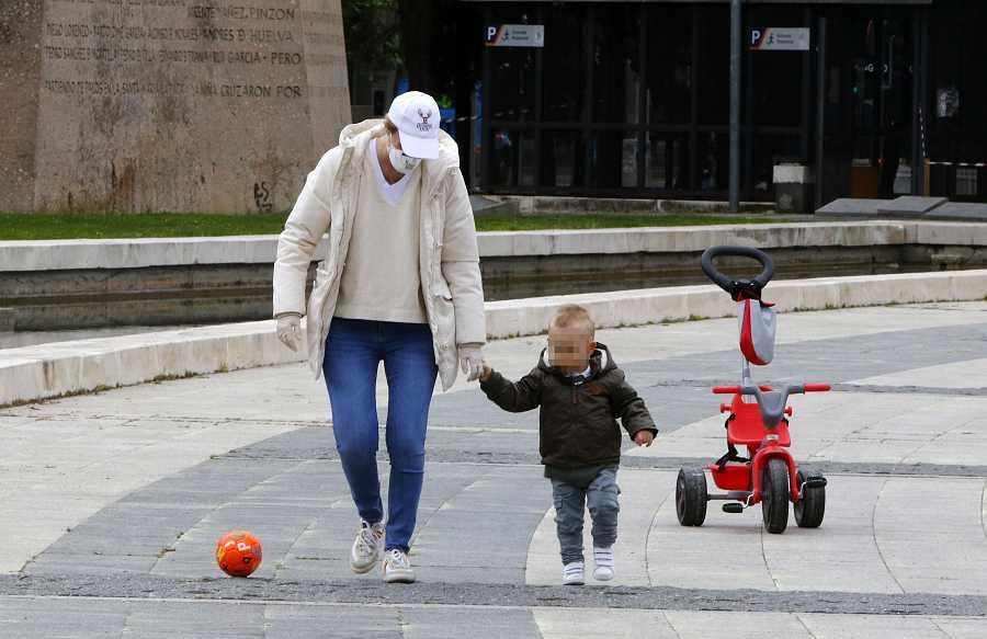 María Zurita juega con su hijo en una plaza con una pelota durante el alivio de la cuarentena para los niños
