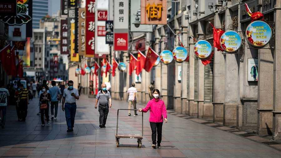 Varias personas pasean por las calles de Guangzhou, China