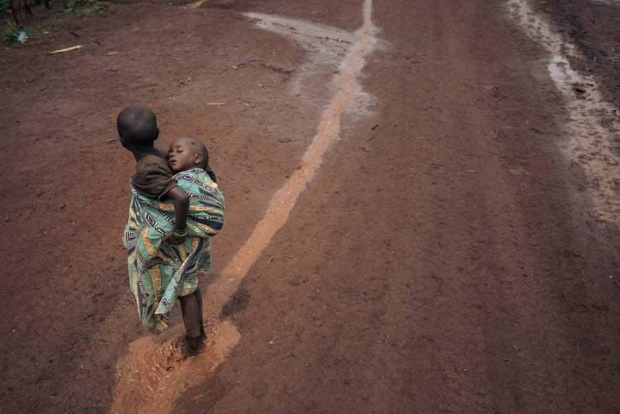 Dos niños caminan sobre charcos de lluvia en el campo de Rho.