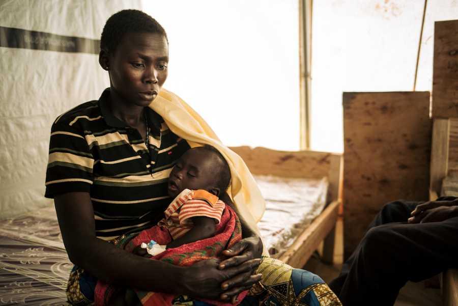 Honorine, de 31 años, sostiene a su hija de 7 meses en la clínica móvil en el campo de desplazados de Rho.