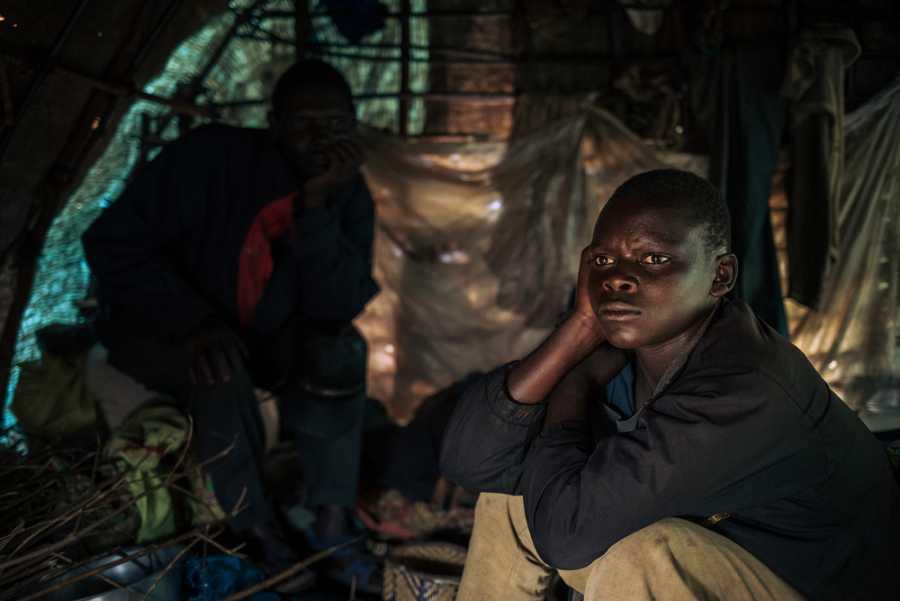 Benjamin, 16 años, sentado junto a su padre en su refugio de plástico en el campo de desplazados de Rho.