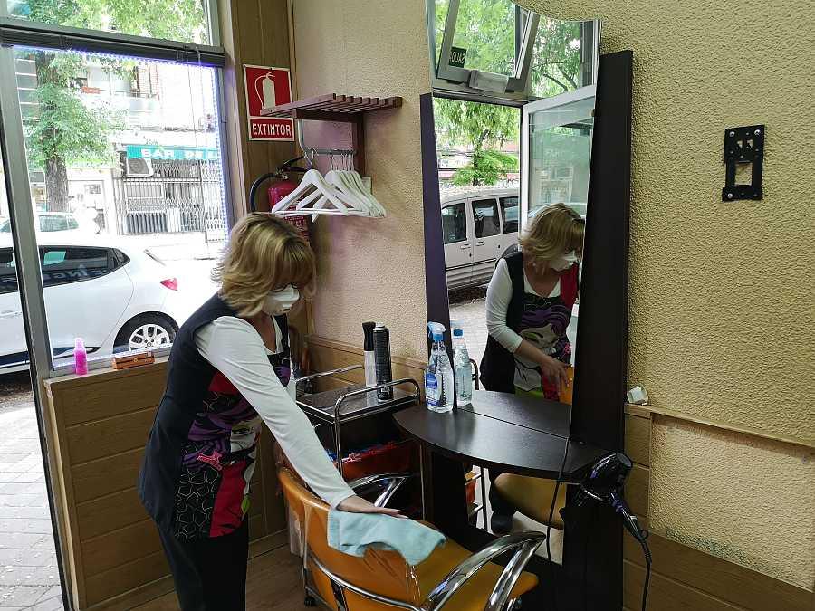 La dueña de una peluquería limpia uno de los sillones antes de abrir el local