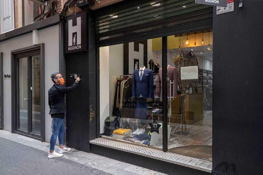 El propietario de una tienda de ropa de la calle jabonerias de Murcia, levanta la persiana