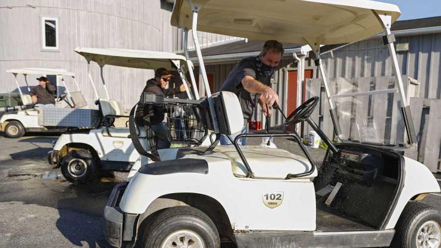 Imagen: Operarios desinfectan un buggie en un campo de golf estadounidense
