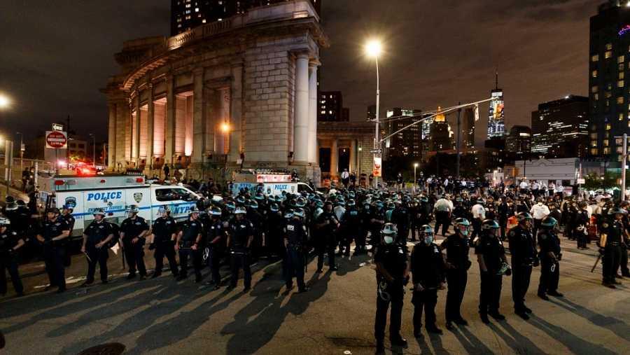 Agentes de policía de Nueva York hacen guardia en el puente de Manhattan para hacer cumplir el toque de queda y evitar disturbios.