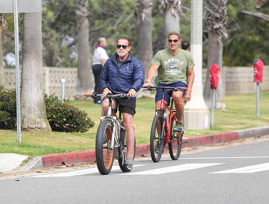 Los actores Arnold Schwarzenegger y Ralf Moeller montan juntos en bici en Los Ángeles, California.
