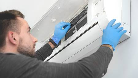 Una persona con guantes revisa un aparato doméstico de aire acondicionado.