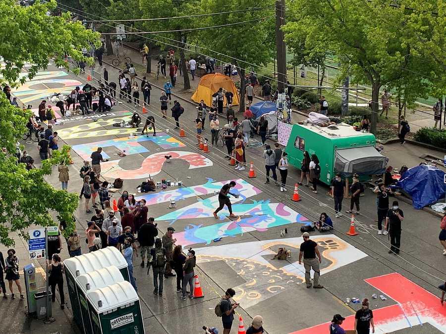 Los manifestantes pintan un mural en las calles de la