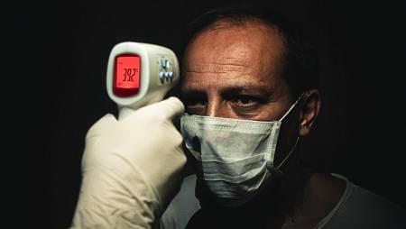 Toma de temperatura con un termómetro de rayos infrarrojos a un hombre con mascarilla sanitaria.