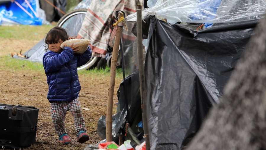 Una niña lleva una bolsa de comida en un campamento improvisado donde permanecen migrantes venezolanos sin empleo y sin hogar en Bogotá, Colombia en junio de 2020.
